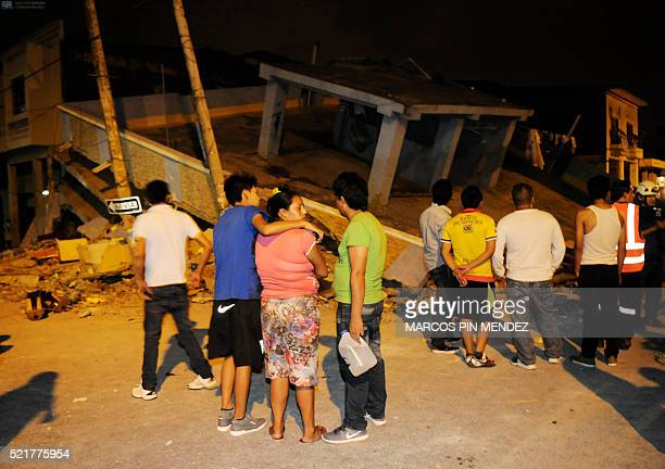This picture shows people gathering outside a collapsed home after an earthquake in the city of Guayaquil on April 17 2016 At least 77 people were...