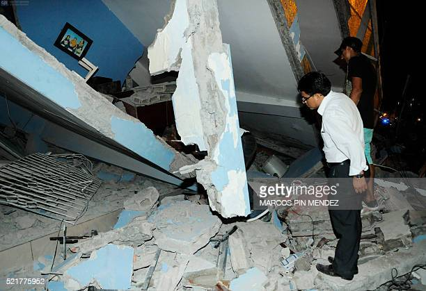 This picture shows people looking at a collapsed home after an earthquake in the city of Guayaquil on April 17 2016 At least 77 people were killed...