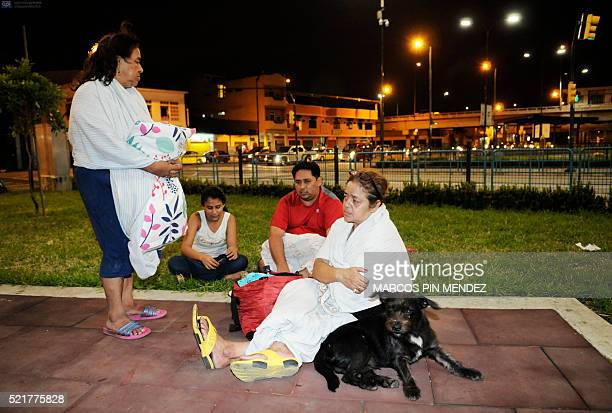 This picture shows people resting in a park after an earthquake in the city of Guayaquil on April 17 2016 At least 77 people were killed when a...