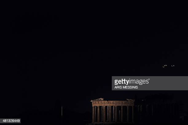 This picture shows the ancient Temple of Parthenon atop the Acropolis hill in the dark during the Earth Hour initiative in Athens on March 29 2014...