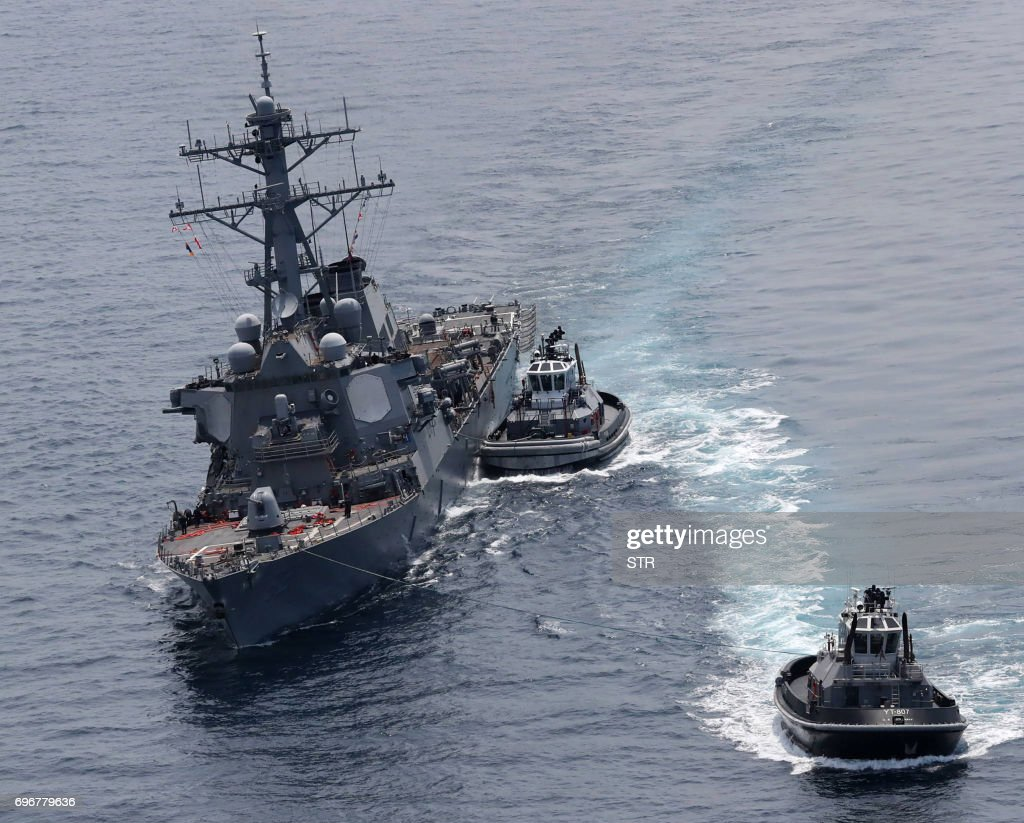 This picture shows the guided missile destroyer USS Fitzgerald next to tugboats off the Shimoda coast after it collided with a Philippine-flagged container ship on June 17, 2017. The US Navy destroyer collided with ACX Crystal cargo ship off the coast of Japan, leaving seven crew members from the American vessel unaccounted for, the Japanese Coast Guard said. / AFP PHOTO / JIJI PRESS / STR / Japan OUT