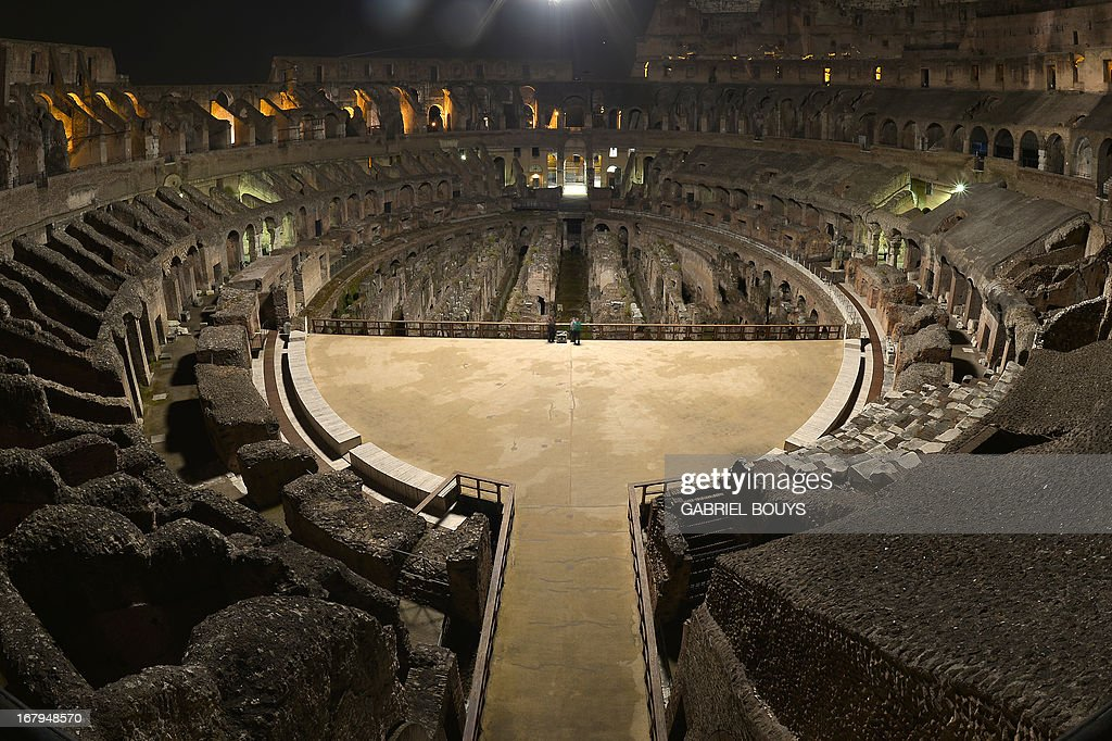 This picture shows the inside of the Colosseum during a preview of the night tour 'The moon over the colosseum' late on May 2, 2013 in Rome. 'The moon over the colosseum', a guided tour at night of the Flavian Amphitheatre will take place from May 5 to October 6, 2013 every Thursdays and Saturdays. AFP PHOTO / GABRIEL BOUYS