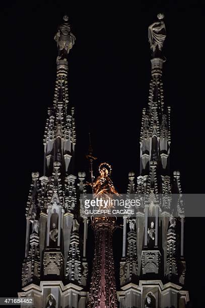 This picture shows the Madoninna a statue of the Virgin Mary atop Milan Cathedral during the EXPO2015 'The Opening' ceremony in Piazza Duomo on April...