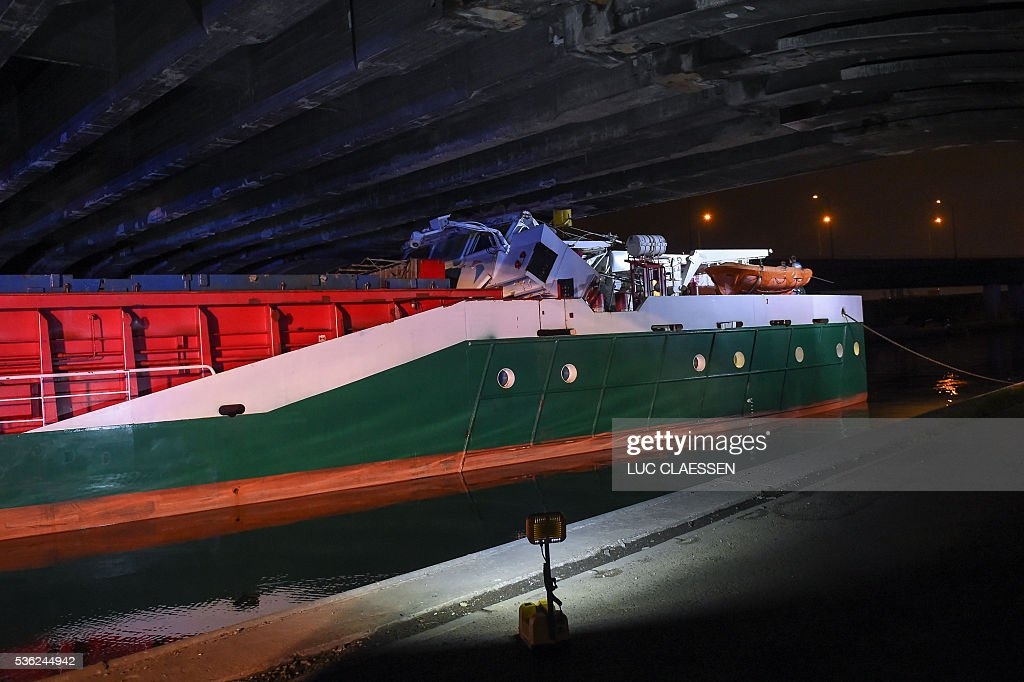 This picture shows the scene of an accident where a wood transportation ship hit a bridge over the Albert Canal, early on June 1, 2016 in Antwerpen, in which at least one person was severely injured. The ship's wheelhouse was totally destroyed in the accident that occured late on May 31. / AFP / Belga / LUC CLAESSEN / Belgium OUT