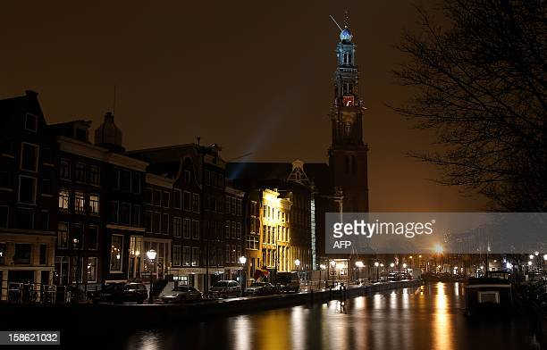 This picture shows the Westerkerk and Amsterdam's typical canals on a rainy night in Amsterdam on December 21 2012 AFP PHOTO / ALEXANDER KLEIN