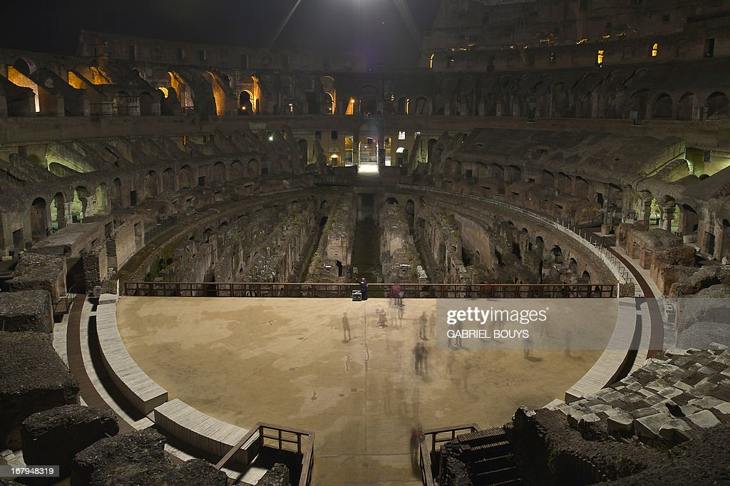 This picture shows visitors inside of the Colosseum during a preview of the night tour 'The moon over the colosseum' late on May 2, 2013 in Rome. 'The moon over the colosseum', a guided tour at night of the Flavian Amphitheatre will take place from May 5 to October 6, 2013 every Thursdays and Saturdays. AFP PHOTO / GABRIEL BOUYS