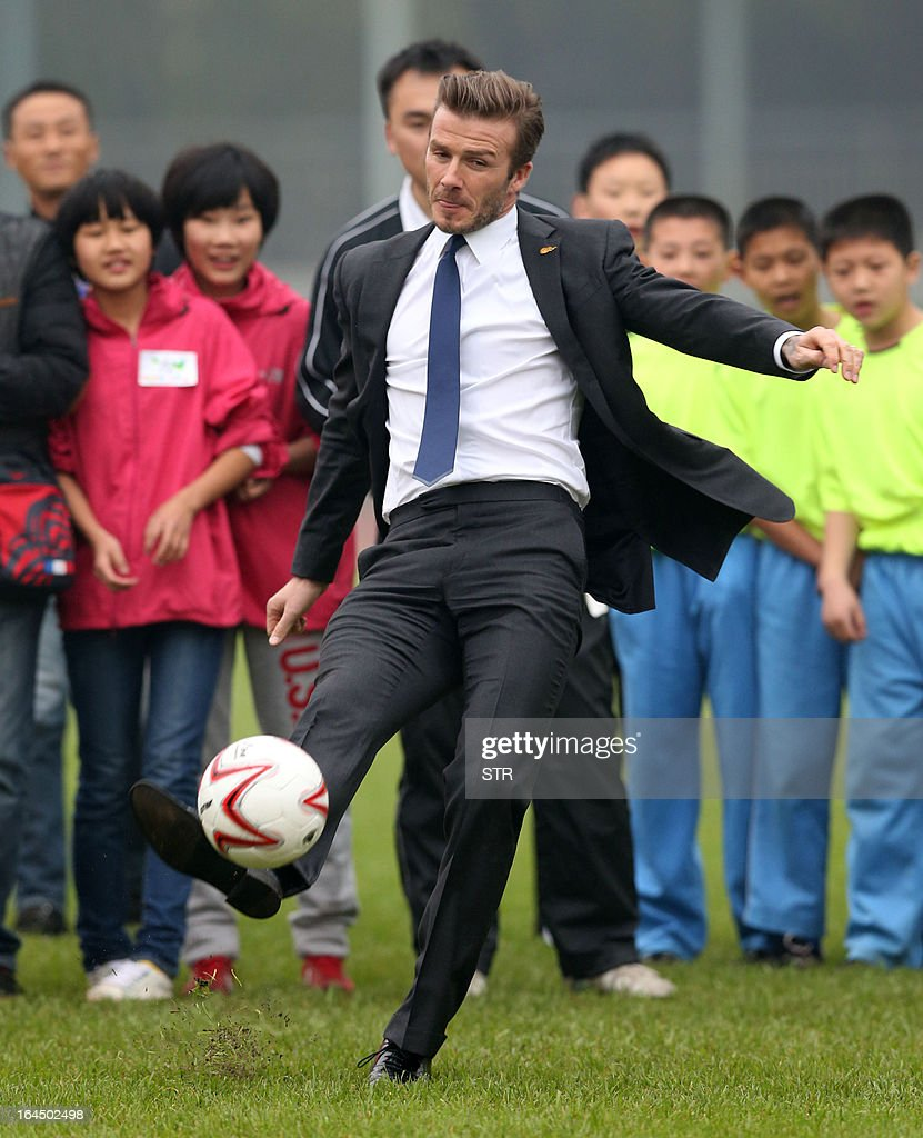 This picture take on March 23, 2013 shows football superstar David Beckham (front C) kicking a football during a meeting with young players and fans in a stadium in Wuhan, central China's Wuhan province. Beckham raised the prospect of one last stop on his global football journey on March 20, refusing to rule out playing in China after his contract with Paris Saint-Germain ends. CHINA