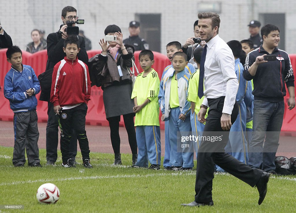 This picture take on March 23, 2013 shows football superstar David Beckham (front R) kicking a football during a meeting with young players and fans in a stadium in Wuhan, central China's Wuhan province. Beckham raised the prospect of one last stop on his global football journey on March 20, refusing to rule out playing in China after his contract with Paris Saint-Germain ends. CHINA