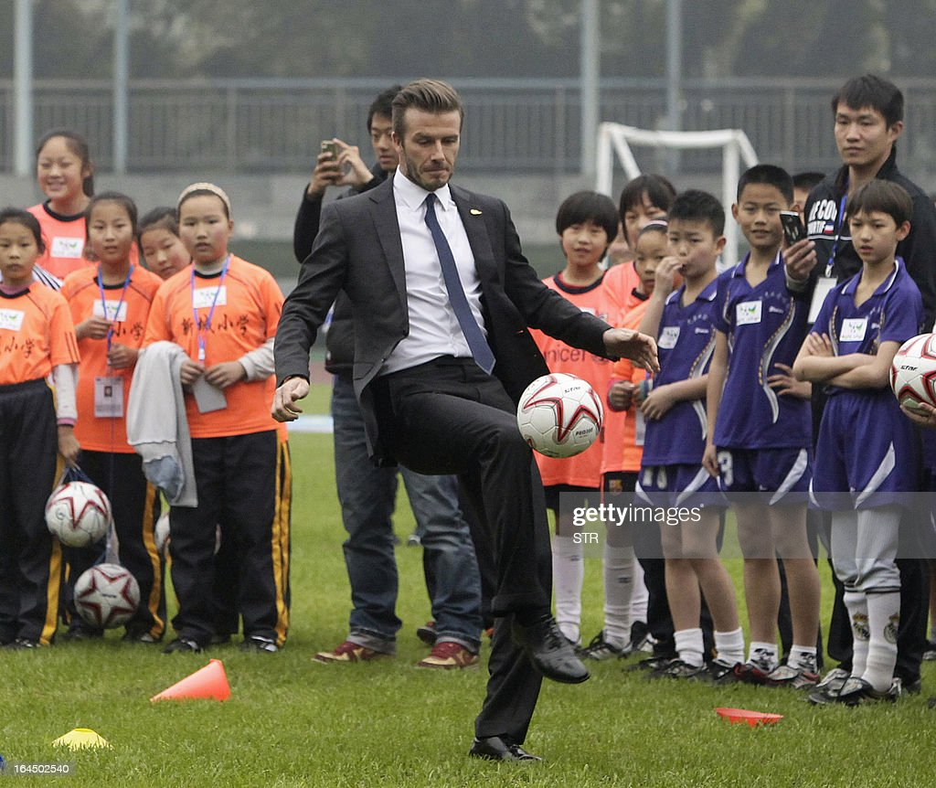 This picture take on March 23, 2013 shows football superstar David Beckham (C) during a game with young players in a stadium in Wuhan, central China's Wuhan province. Beckham raised the prospect of one last stop on his global football journey on March 20, refusing to rule out playing in China after his contract with Paris Saint-Germain ends. CHINA OUT AFP PHOTO