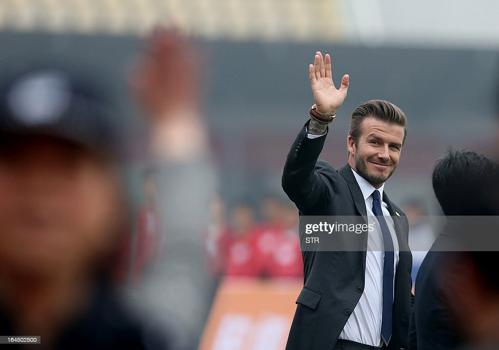 This picture take on March 23, 2013 shows football superstar David Beckham (R) waving during a meeting with young players and fans in a stadium in Wuhan, central China's Wuhan province. Beckham raised the prospect of one last stop on his global football journey on March 20, refusing to rule out playing in China after his contract with Paris Saint-Germain ends. CHINA