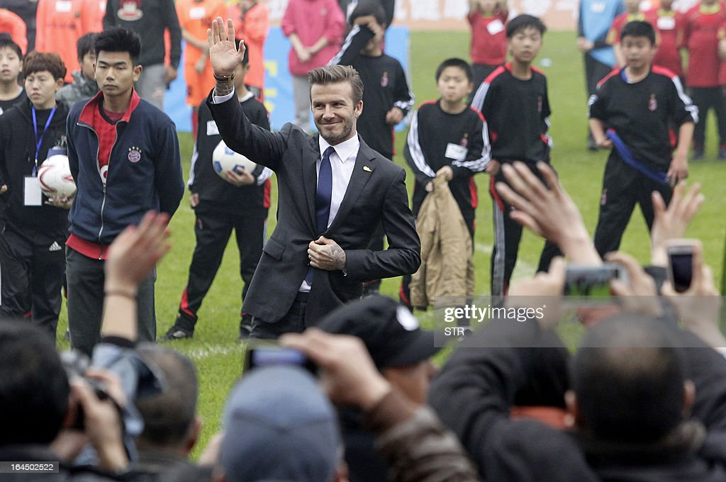This picture take on March 23, 2013 shows football superstar David Beckham (C) waving during a meeting with young players and fans in a stadium in Wuhan, central China's Wuhan province. Beckham raised the prospect of one last stop on his global football journey on March 20, refusing to rule out playing in China after his contract with Paris Saint-Germain ends. CHINA OUT AFP PHOTO