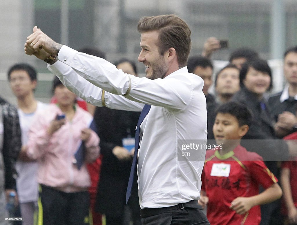 This picture take on March 23, 2013 shows football superstar David Beckham gesturing during a meeting with young players and fans in a stadium in Wuhan, central China's Wuhan province. Beckham raised the prospect of one last stop on his global football journey on March 20, refusing to rule out playing in China after his contract with Paris Saint-Germain ends. CHINA