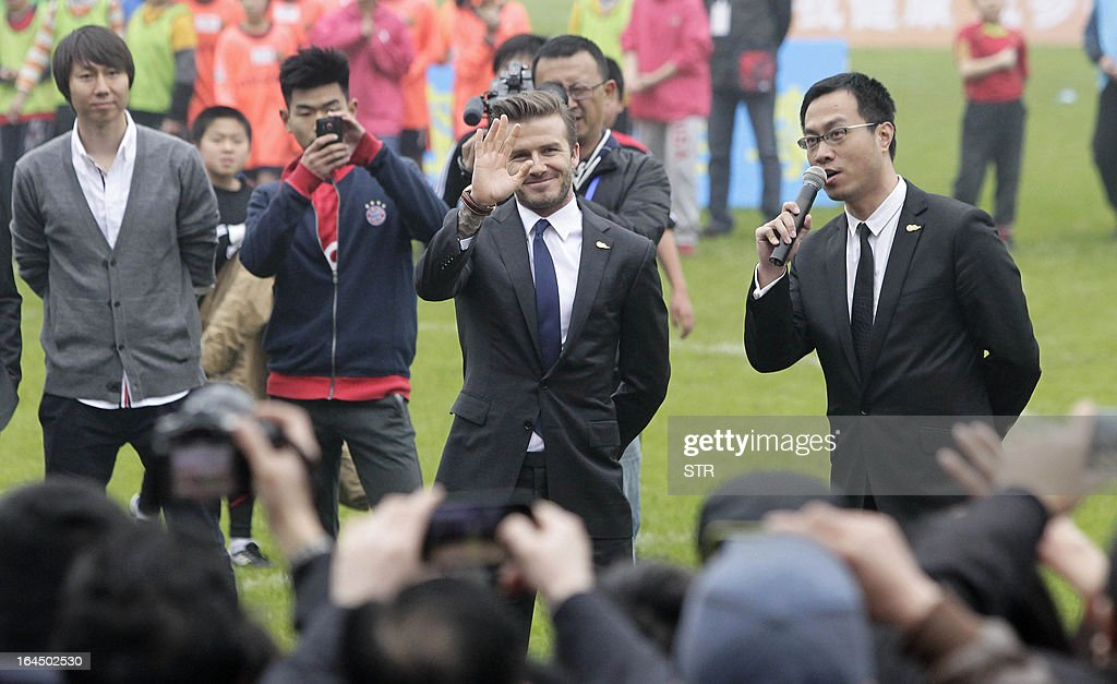 This picture take on March 23, 2013 shows football superstar David Beckham (C) waving during a meeting with young players and fans in a stadium in Wuhan, central China's Wuhan province. Beckham raised the prospect of one last stop on his global football journey on March 20, refusing to rule out playing in China after his contract with Paris Saint-Germain ends. CHINA