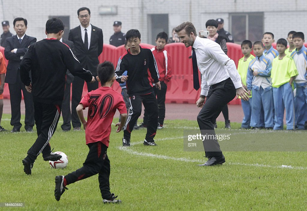This picture take on March 23, 2013 shows football superstar David Beckham ( R) playing football with young players in a stadium in Wuhan, central China's Wuhan province. Beckham raised the prospect of one last stop on his global football journey on March 20, refusing to rule out playing in China after his contract with Paris Saint-Germain ends. CHINA OUT AFP PHOTO