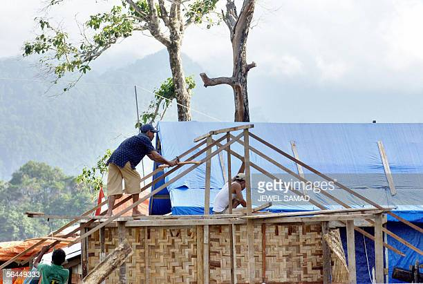 This picture taken 01 December 2005 shows Acehnese people building a new house in the outskirts of Banda Aceh After the last year devastating tsunami...