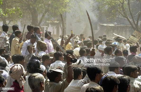 This picture taken 01 March 2002 shows a Hindu mob waving swords at an opposing Muslim mob during communal riots in Ahmedabad India's incoming prime...