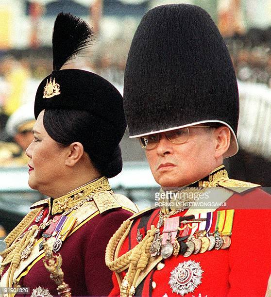This picture taken 03 December 1996 shows Thai King Bhumibol Adulyadej and Queen Sirikit sit together during a review of the Thai troops in Bangkok...