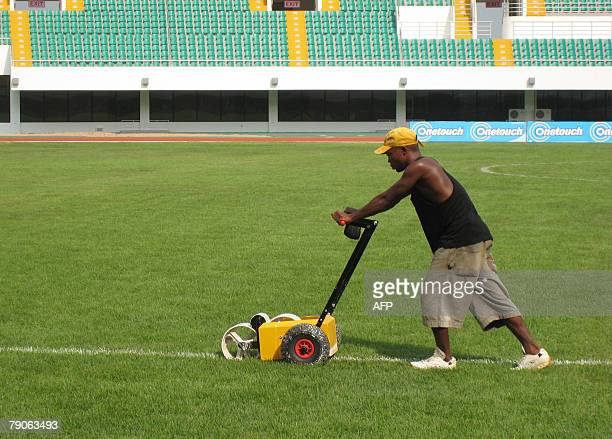 This picture taken 12 January 2008 in Sekondi shows an employee marking the lawn of the Essipong Sports Stadium a few days before the opening of the...