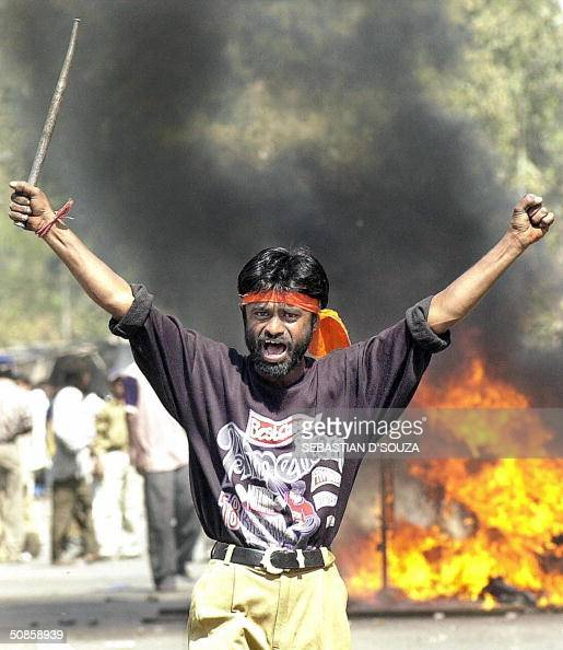 This picture taken 28 February 2002 shows a Bajranj Dal activist armed with a iron stick shouting slogans against muslims as they went burning muslim...