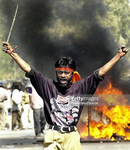 This picture taken 28 February 2002 shows an IndianBajranj Dal activist armed with a iron stick shouting slogans against muslims as they went burning...