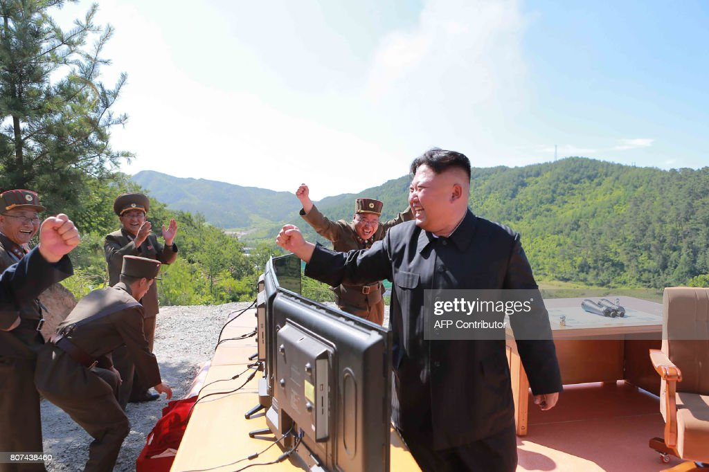 This picture taken and released on July 4, 2017 by North Korea's official Korean Central News Agency (KCNA) shows North Korean leader Kim Jong-Un (R) reacting after the test-fire of the intercontinental ballistic missile Hwasong-14 at an undisclosed location. North Korea declared on July 4 it had successfully tested its first intercontinental ballistic missile -- a watershed moment in its push to develop a nuclear weapon capable of hitting the mainland United States. / AFP PHOTO / KCNA VIA KNS / STR / South Korea OUT / REPUBLIC OF KOREA OUT ---EDITORS NOTE--- RESTRICTED TO EDITORIAL USE - MANDATORY CREDIT 'AFP PHOTO/KCNA VIA KNS' - NO