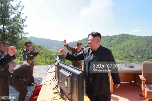 This picture taken and released on July 4 2017 by North Korea's official Korean Central News Agency shows North Korean leader Kim JongUn reacting...