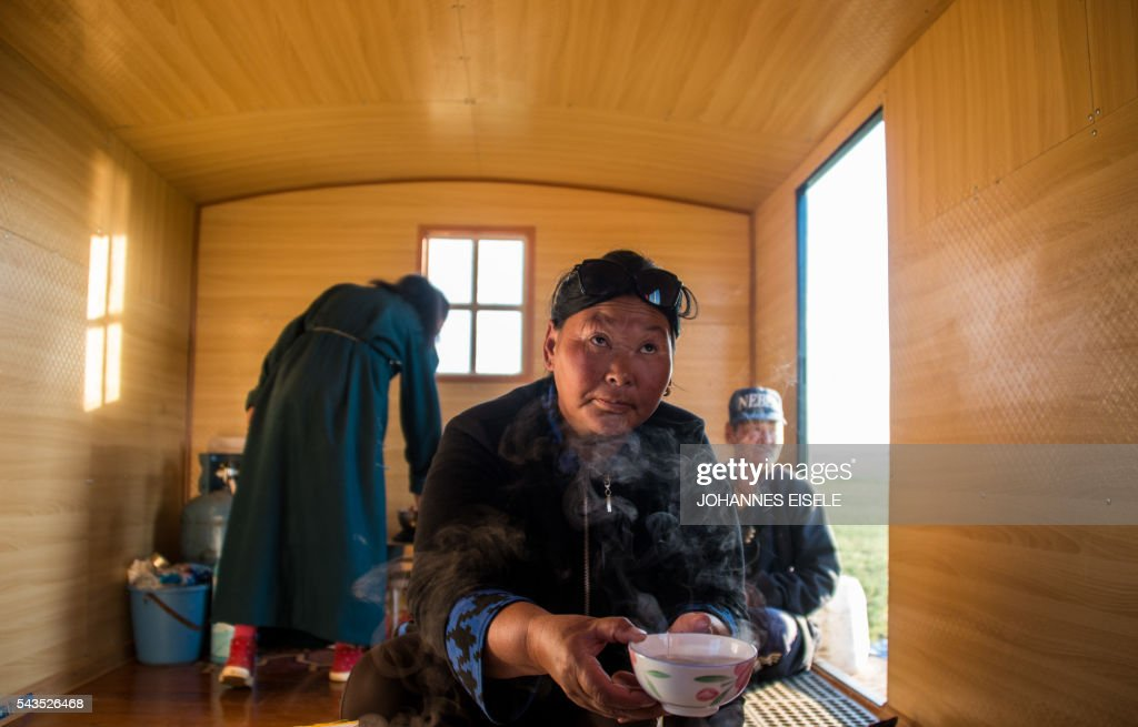 This picture taken early morning on June 29, 2016 shows herder Dambiin Otgontsetseg holding a bowl of tea in her mobile home in the Gobi desert near Luusiin. Mongolians went to the polls across their sprawling, sparsely-populated country on June 29 as it struggles to benefit from its vast natural resources amid disputes over foreign investment and slumping demand from neighbouring China. Across the country -- more than twice the size of France, but with a population of only three million -- trucks with mobile ballot boxes crisscrossed the vast steppe to enable the sick and elderly to vote, while herders and others streamed to polling stations in set up in gers,traditional Mongolian tents. Mongolia-election-politics by Ben Dooley