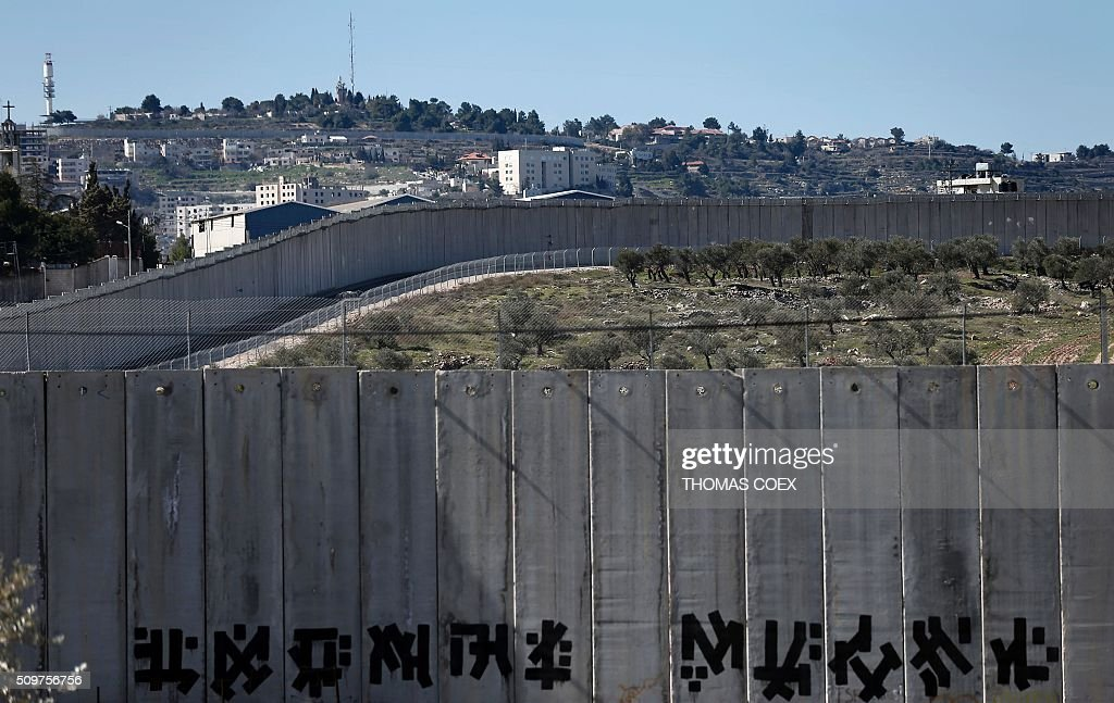 This picture taken from Jerusalem shows Israel's controversial separation barrier dividing Jerusalem and the West Bank town of Bethlehem, on February 12, 2016. / AFP / THOMAS COEX