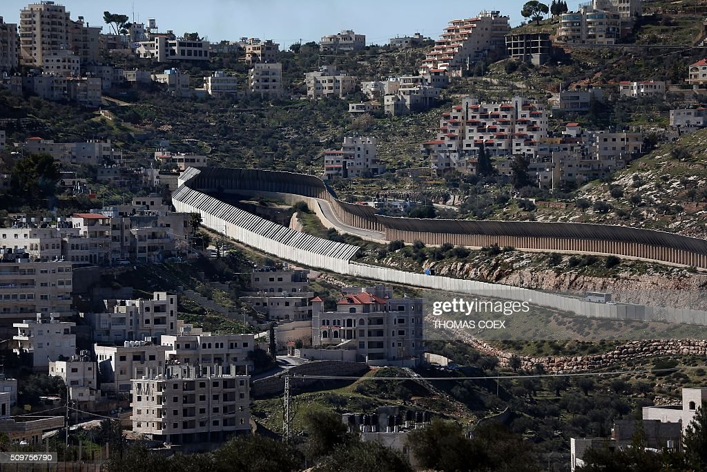 This picture taken from Jerusalem shows the protected road driving through the West Bank town of Bethlehem leading to the Israeli Gush Etzion settlement block and the West Bank city of Hebron, on February 12, 2016. / AFP / THOMAS COEX