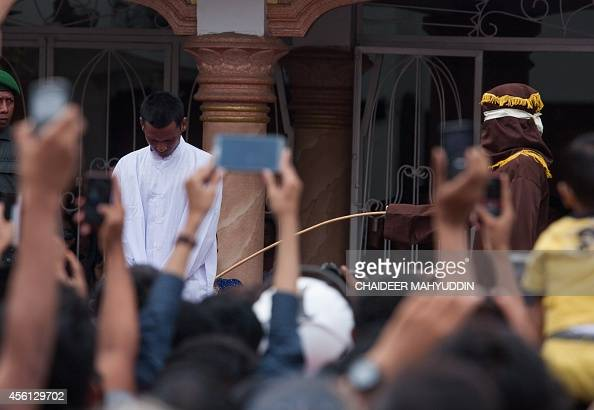 This picture taken in Banda Aceh on September 19 2014 shows a hooded official caning an Aceh man for gambling in Aceh Lawmakers in Indonesia's Aceh...