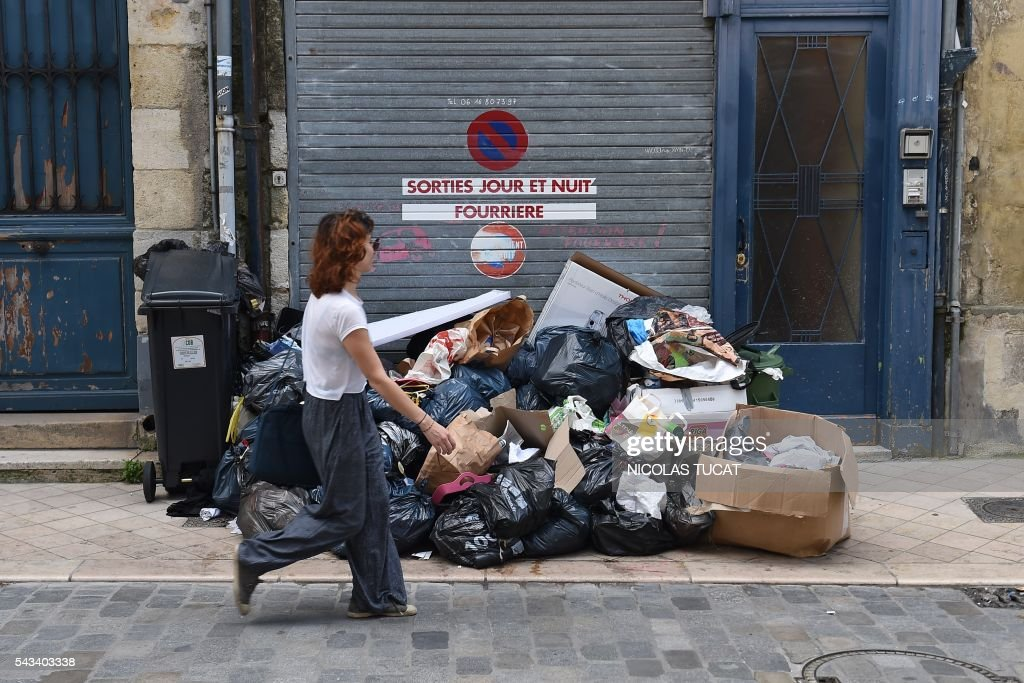 This picture taken in Bordeaux on June 28, 2016 shows wastes overflowing the dustbins. The garbage collectors are on strike in Bordeaux since seven days, as unions have called repeated strikes and marches against controversial labour reforms, forced through by the government of Socialist President Francois Hollande. / AFP / NICOLAS