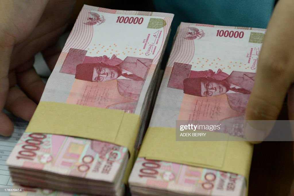 This picture taken in Jakarta on August 28, 2013 shows an Indonesian clerk handling stacks of Indonesian rupiah notes at a money changer office in Jakarta. Indonesia's central bank hiked interest rates for the third time in three month on August 28, at an unscheduled meeting after a plunge in the rupiah and stocks.