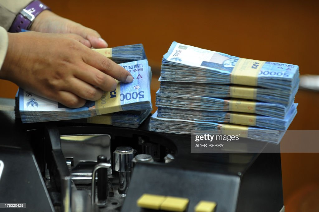 This picture taken in Jakarta on August 28, 2013 shows an Indonesian clerk handling stacks of Indonesian rupiah notes at a money changer office in Jakarta. Indonesia's central bank hiked interest rates for the third time in three month on August 28, at an unscheduled meeting after a plunge in the rupiah and stocks. AFP PHOTO / ADEK BERRY