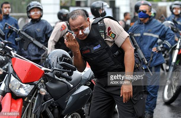 This picture taken in Jakarta on March 27 2012 shows an Indonesian police officer applying toothpaste on his face as clashes broke out between police...