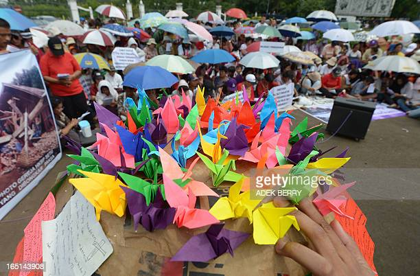 This picture taken in Jakarta on March 31 2013 shows a man holding origami cranes while Indonesian Christians hold an Easter service outside of the...
