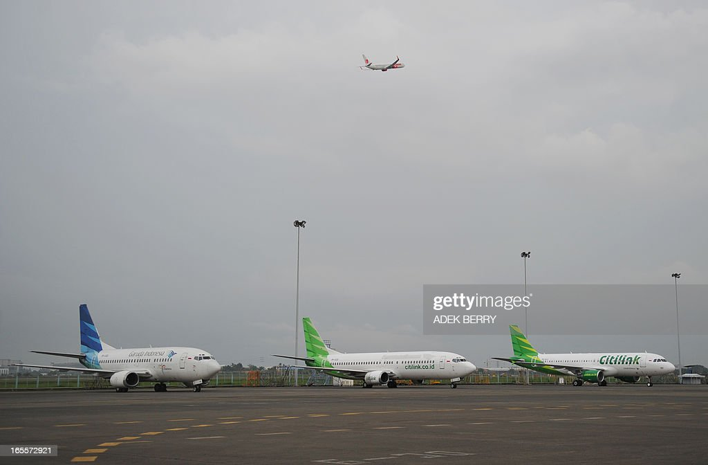 This picture taken in Tangerang on April 4, 2013 shows a Lion Boeing plane flying over the Sukarno-Hatta airport in Tangerang as a Citilink Airbus A320-214 (1st R) and two others Boeing planes (C and 1st L) are parked. A new rivalry between the worlds's biggest planemakers is heating up in Indonesia after a record deal for Airbus in a market with huge potential that until now has been a 'fortress' for Boeing. Indonesians are increasingly relying on air travel to link the archipelago of 17,000-odd islands, with up to 900 new planes set to be delivered to Indonesia in the next decade, according to the government. The potential is massive -- only six percent of Indonesians have travelled by air, according to officials, in a nation of 240 million people that has consistently clocked annual economic growth above six percent. AFP PHOTO / ADEK BERRY
