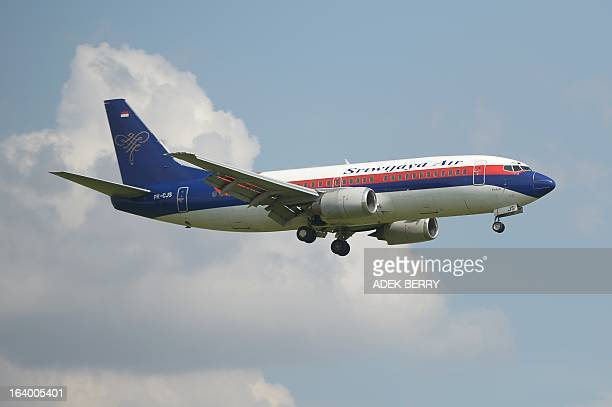This picture taken in Tangerang on March 18 2013 shows an Indonesian Sriwijaya air plane preparing for landing over the SukarnoHatta airport in...