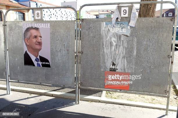 This picture taken in Toulouse on April 18 shows defaced electoral posters of French presidential election candidates including one showing French...