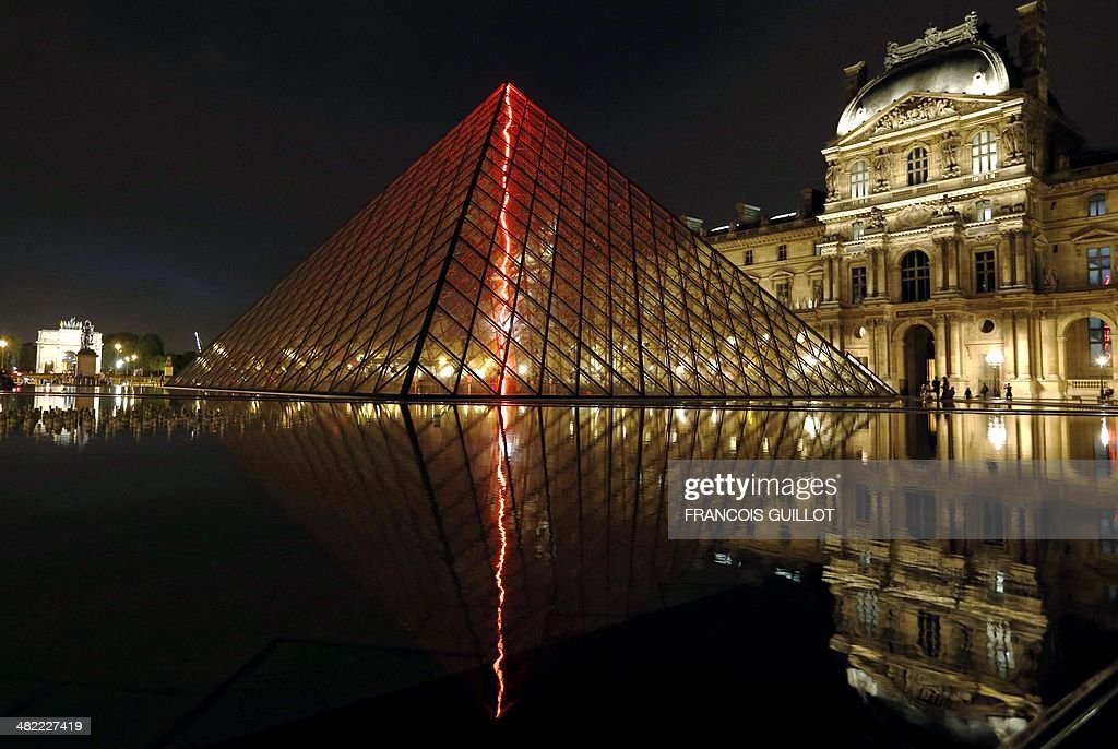 This picture taken late on April 2, 2014 shows 'Sous le plus grand chapiteau du monde' (Under the world's biggest big top) an artistic performance by French artist Claude Leveque at the Pyramid du Louvre in Paris. The red neon lightning will shine for 18 months.
