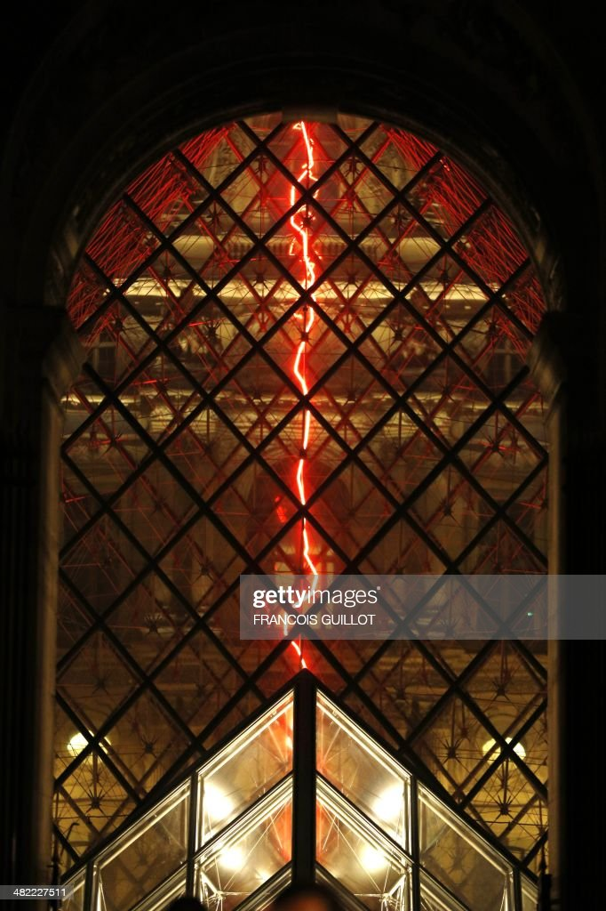 This picture taken late on April 2, 2014 shows 'Sous le plus grand chapiteau du monde' (Under the world's biggest big top) an artistic performance by French artist Claude Leveque at the Pyramid du Louvre in Paris. The red neon lightning will shine for 18 months. AFP PHOTO/FRANCOIS GUILLOT = RESTRICTED TO EDITORIAL USE, MANDATORY MENTION OF THE ARTIST UPON PUBLICATION, TO ILLUSTRATE THE EVENT AS SPECIFIED IN THE CAPTION