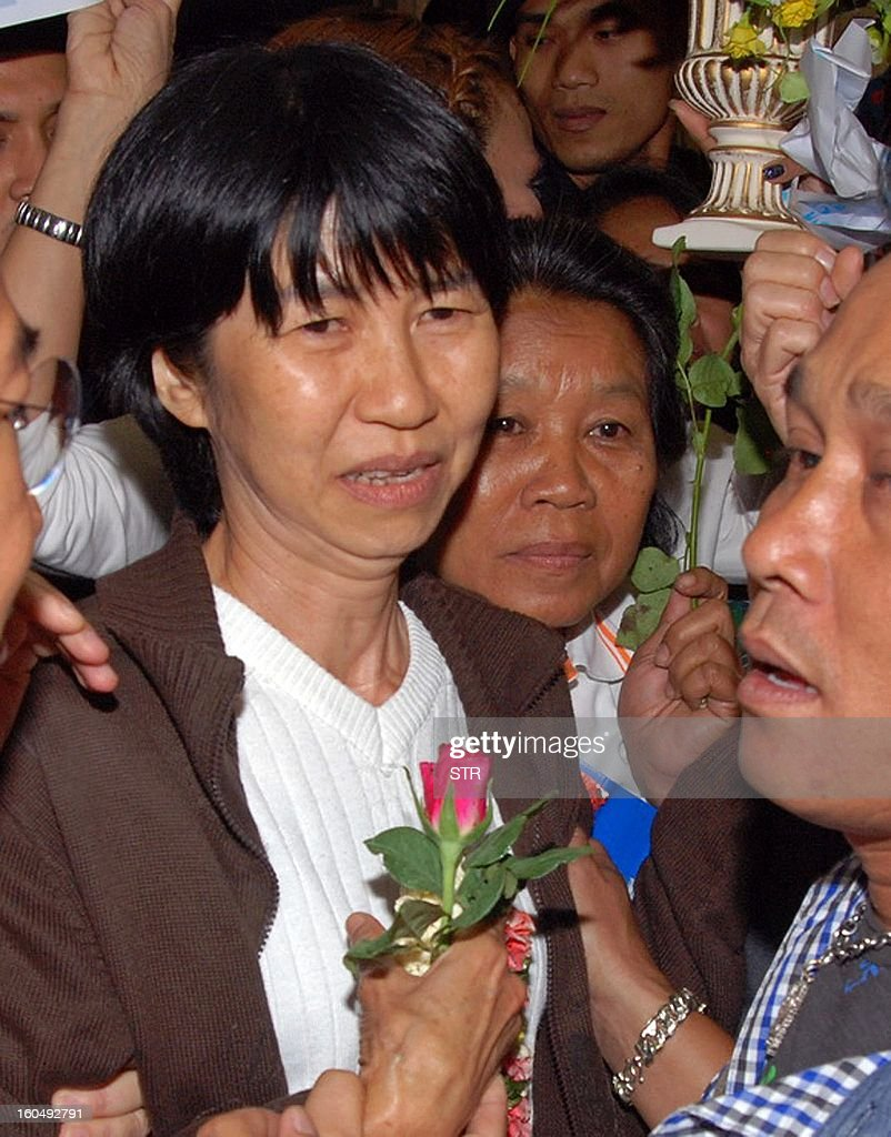 This picture taken late on February 1, 2013 shows Thai 'Yellow Shirt' activist Ratree Pipattanapaibul (C) being greeted by friends upon her arrival at Suvarnabhumi airport in Bangkok. Ratree was released from a Cambodian jail on February 1 as she received a royal pardon on the occasion of the funeral of former Cambodian king Norodom Sihanouk. Ratree was sentenced to jail in 2011 for illegally entering Cambodia and espionage. AFP PHOTO