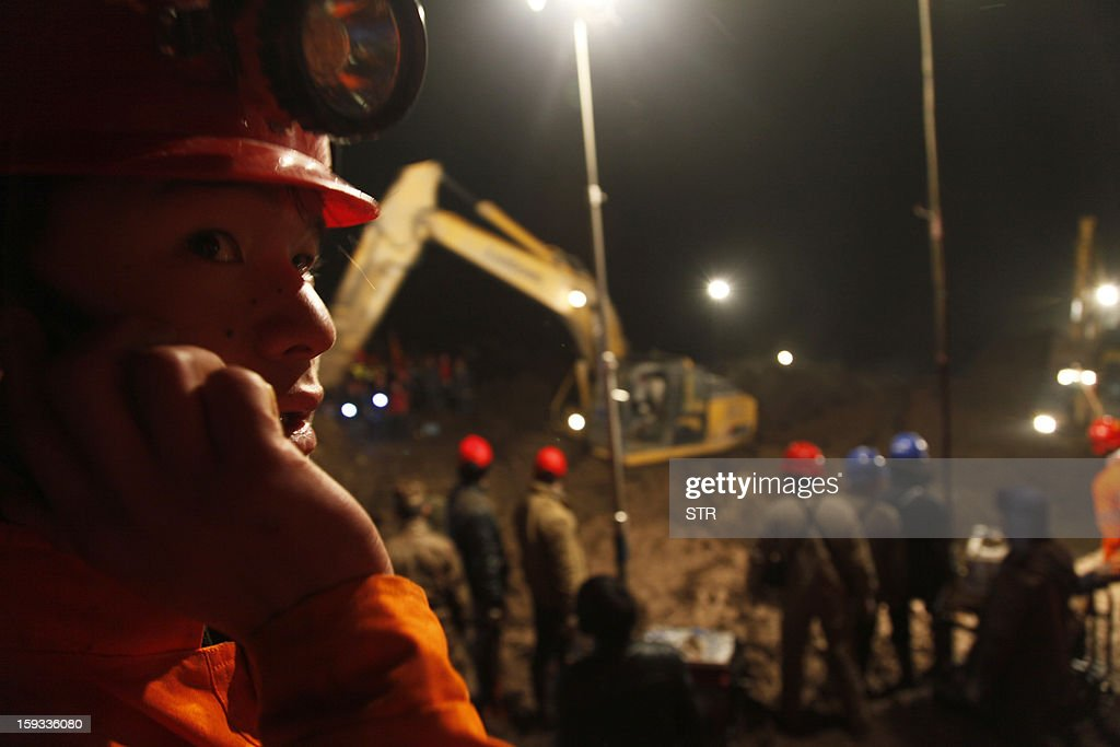 This picture taken late on January 11, 2013 shows a rescuer (L) making a phone call during the search for buried residents in disaster-hit Gaopo village, southwest China's Yunnan province. Three people remain missing after a landslide which killed 43, including seven from a single family, struck a remote village in southwestern China, state media said on January 12. CHINA OUT AFP PHOTO
