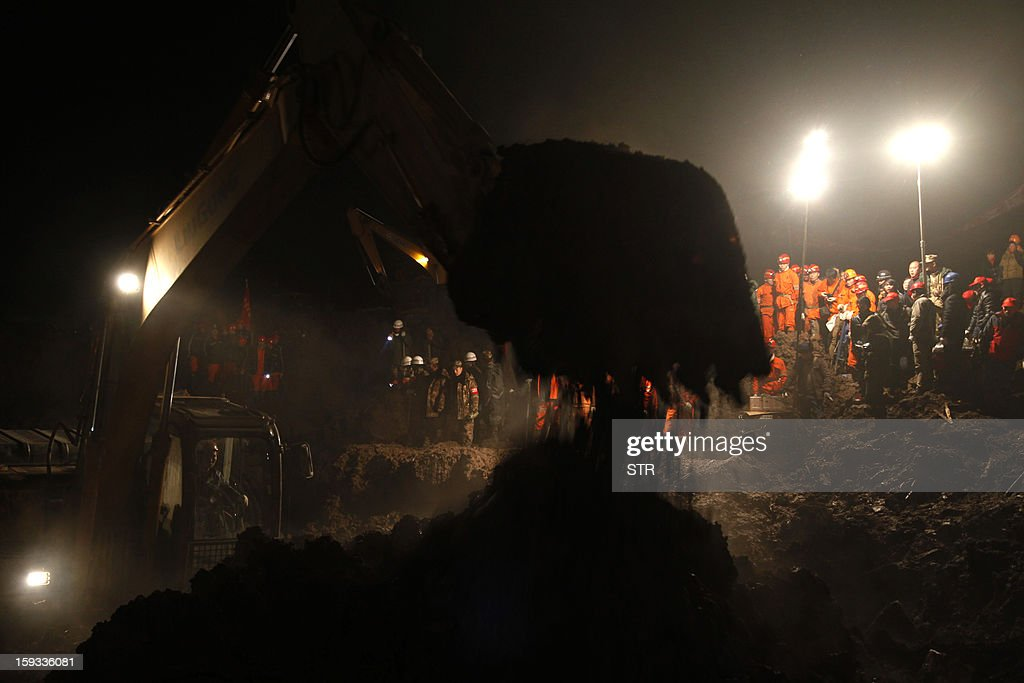 This picture taken late on January 11, 2013 shows heavy machinery in use as rescuers search for buried residents in disaster-hit Gaopo village, southwest China's Yunnan province. Three people remain missing after a landslide which killed 43, including seven from a single family, struck a remote village in southwestern China, state media said on January 12. CHINA