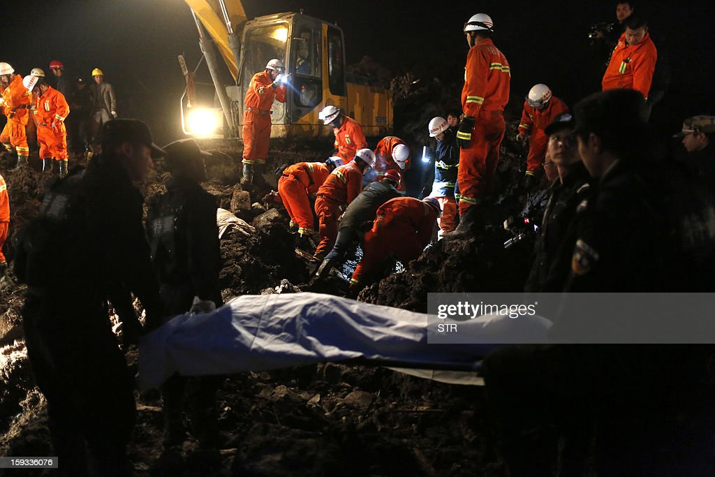 This picture taken late on January 11, 2013 shows rescuers carrying a dead body (front C) in disaster-hit Gaopo village, southwest China's Yunnan province. Three people remain missing after a landslide which killed 43, including seven from a single family, struck a remote village in southwestern China, state media said on January 12. CHINA