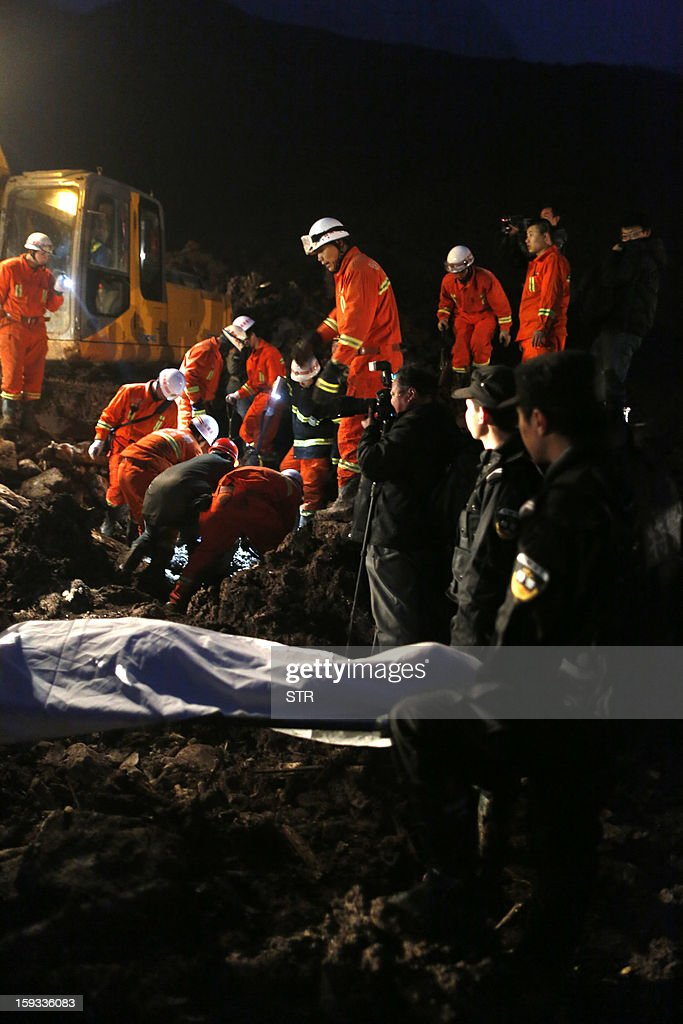 This picture taken late on January 11, 2013 shows rescuers carrying a dead body (front C) in disaster-hit Gaopo village, southwest China's Yunnan province. Three people remain missing after a landslide which killed 43, including seven from a single family, struck a remote village in southwestern China, state media said on January 12. CHINA OUT AFP PHOTO