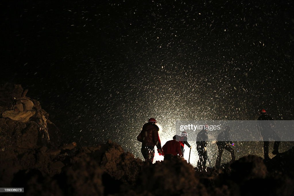 This picture taken late on January 11, 2013 shows rescuers searching for missing residents in disaster-hit Gaopo village, southwest China's Yunnan province. Three people remain missing after a landslide which killed 43, including seven from a single family, struck a remote village in southwestern China, state media said on January 12. CHINA OUT AFP PHOTO