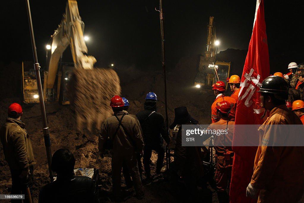 This picture taken late on January 11, 2013 shows rescuers searching for buried residents in disaster-hit Gaopo village, southwest China's Yunnan province. Three people remain missing after a landslide which killed 43, including seven from a single family, struck a remote village in southwestern China, state media said on January 12. CHINA