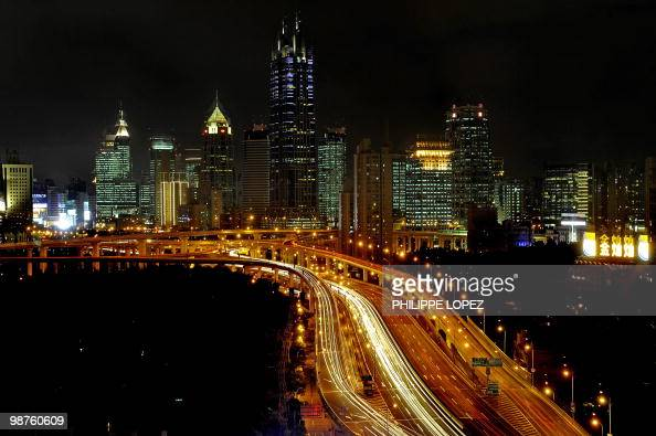 This picture taken late on July 27 2009 shows an illuminated view of residential and business buildings in Shanghai China's biggest home builder...