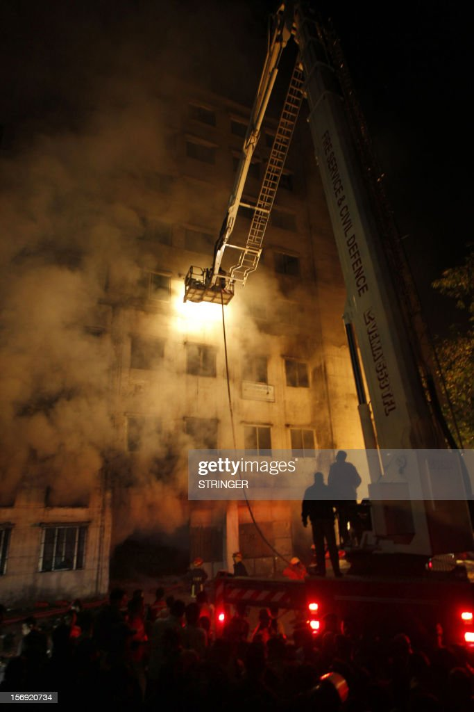 This picture taken on 24 November, 2012 shows Bangladeshi firefighters trying to extinguish a fire at the nine-storey Tazreen Fashion plant in Savar, about 30 kilometres north of Dhaka on November 25, 2012. Rescue workers in Bangladesh recovered 109 bodies on Sunday after a fire tore through a garment factory, forcing many workers to jump from high windows to escape the smoke and flames. AFP PHOTO