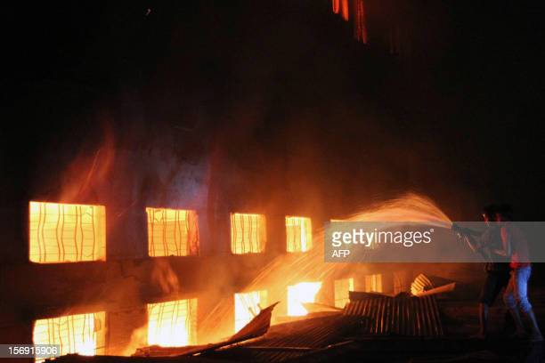 This picture taken on 24 November 2012 shows Bangladeshi people and firefighters trying to extinguish a fire in a garment factory in Savar 30...